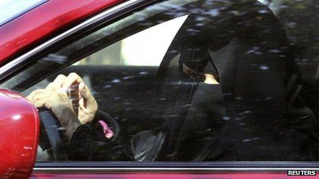 A woman wearing a burka drives a car in Saudi Arabia
