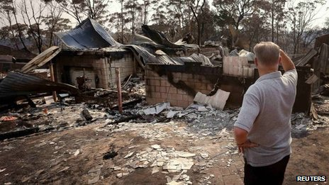 man surveys damage to his house