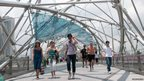Tourists, joggers and office workers crossing Singapore's Helix Bridge