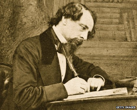 Charles Dickens writing at desk