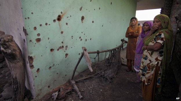 Indian women look at shell marks allegedly caused from firing from Pakistan side at Garkhal village near the India-Pakistan international border, 35 kilometers (22 miles) from Jammu, India, Friday, Oct. 25, 2013