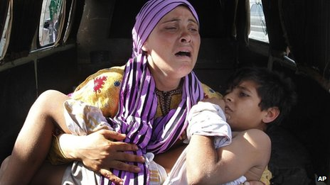 A Syrian mother carrying her injured son escapes