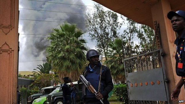 A Kenyan police officer at the entrance of a building in the vicinity of the besieged Westgate shopping mall in Nairobi from where a column of smoke rises following a loud explosion - 23 September 2013