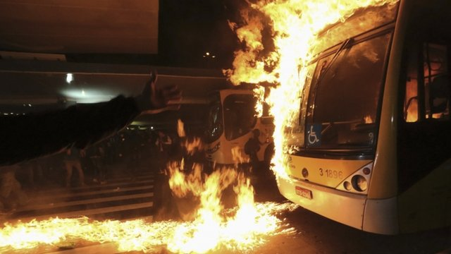 Protester gestures to bus on fire
