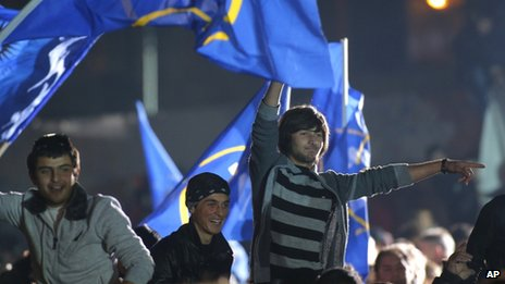 People react and wave flags during a pre-election concert to support presidential candidate from the ruling Georgian Dream coalition, Georgy Margvelashvili, in Tbilisi, Georgia,