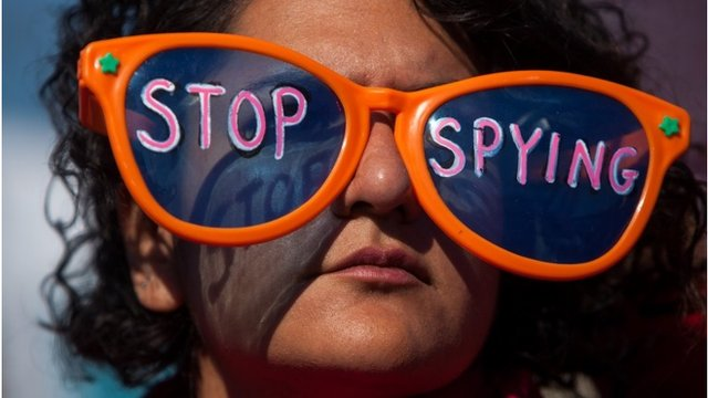 "A woman wearing oversized sunglasses lettered with the words ""stop spying"""