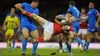 Italy players Mark Minichello (l) and Joshua Mantellato (r) combine to halt Rhys Evans as Wales trail 14-12 at half-time