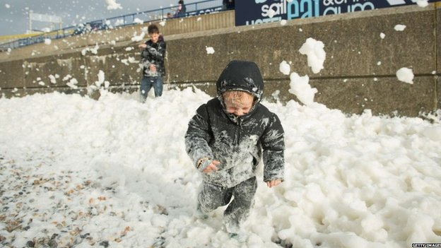 Will Brewer, 4, plays in the foam washed ashore on the Brighton seafront