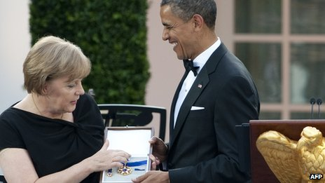 US President Barack Obama presents German Chancellor Angela Merkel with the 2010 Presidential Medal of Freedom during a State Dinner in the Rose Garden at the White House in Washington (7 June 2011)