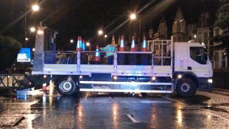 Council workers closing Newport Road in Roath, Cardiff after flooding