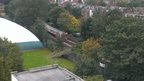 A top shot view of a tree across a train track. A tube train has approached it.