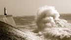 A large wave with huge spray heads towards a harbour wall with a lighthouse on it.