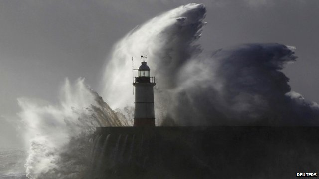 Waves crash against a lighthouse
