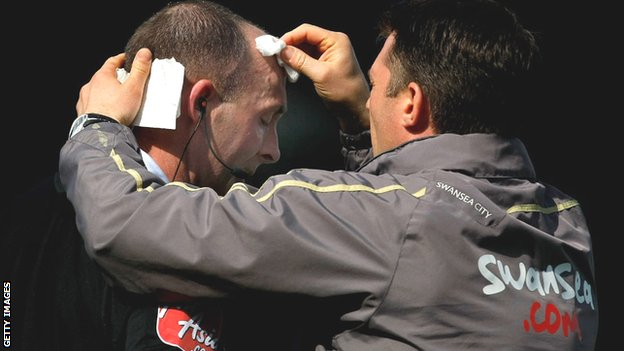 Referee Mike Dean receiving treatment from a member of Swansea City's medical staff after being struck by a coin at Ninian Park in 2009