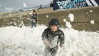 Will Brewer, 4, plays in the foam washed ashore on the Brighton seafront on 27 October, 2013