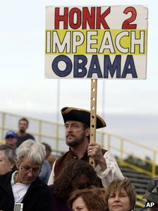 "A man holds a sign reading ""Honk 2 impeach Obama"" at a Republican rally in New Jersey on 12 October 2013"