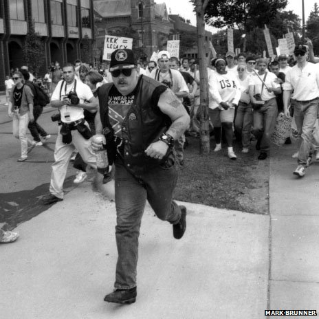 Man being chased by anti-KKK demonstrators