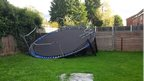 A large round trampoline lies upside down against a garden fence.