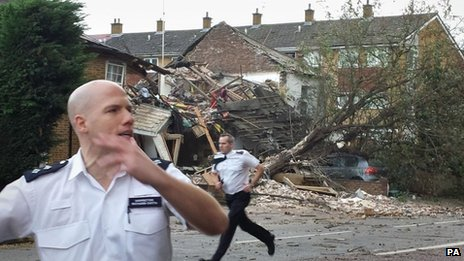 Two police officers rush to secure a residential area after a suspected gas explosion