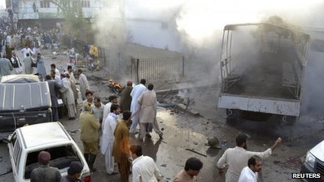 Residents, rescue workers and security officials gather at the site of a bomb blast in Quetta October 10, 2013