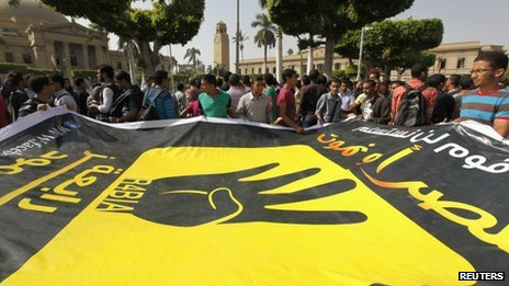Cairo university students and members of the Muslim Brotherhood carry a banner with the four-fingered symbol of Rabaa
