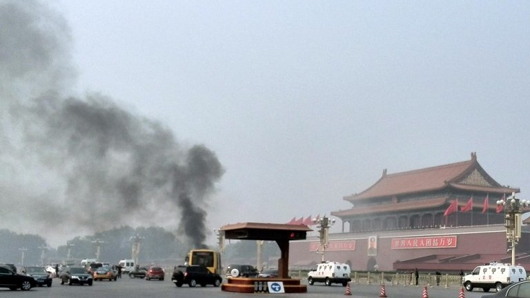 Vehicles travel along Chang'an Avenue as smoke raises in front of a portrait of late Chinese Chairman Mao Zedong at Tiananmen Square in Beijing 28 October 2013