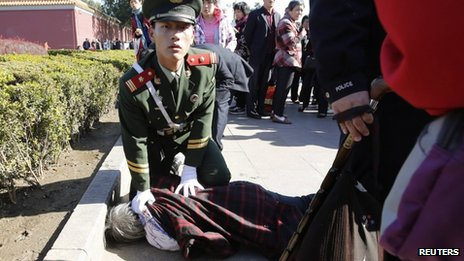A paramilitary policeman detains a woman who threw papers believed to be her petition papers near the main entrance of the Forbidden City. where the car crash happened, in Beijing, China, 29 October 2013