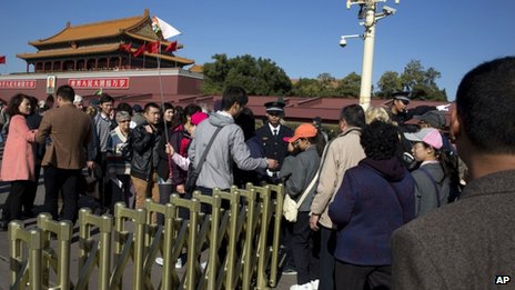 Chinese security personnel direct tourists visiting Tiananmen Gate close to the site of Monday's incident where a car ploughed through a crowd before it crashed and burned in Beijing, China, 29 October 2013