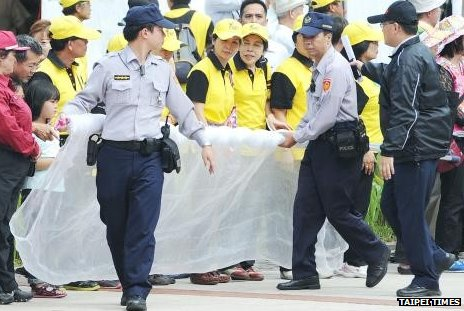 Police officers prepare a net to stop shoes thrown at President Ma Ying-jeou at the Taipei City Hakka Cultural Park on 20 October