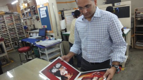 Dhiraj Kacker looking at a wedding album he has published