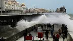 Sea spray crashes over a wall where people are standing. A pier with lights on it and rides is in the background.