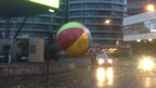 A huge inflatable beach ball on a roundabout following cars with their lights on.