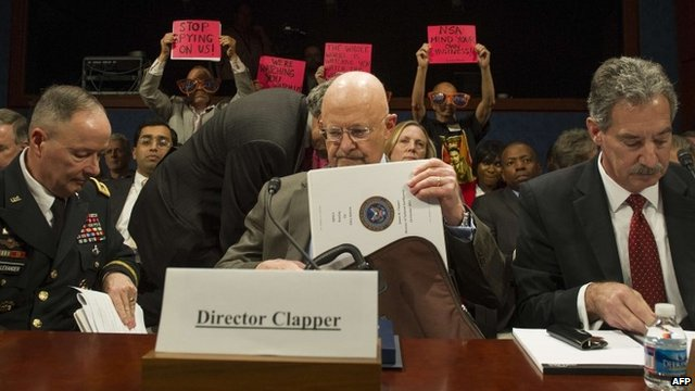 Protesters hold up placards prior to James Clapper testifying