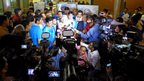 The Queen's Baton arrives amid a media scrum in New Delhi.