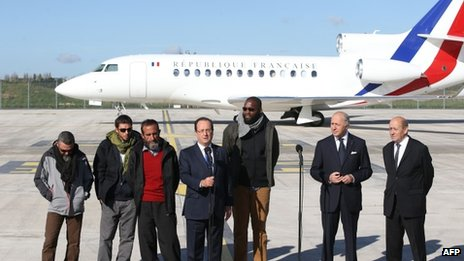 French President Francois Hollande (fourth from the left) is flanked by (left to right) former hostages Marc Feret, Pierre Legrand, Daniel Larribe and Thierry Dol and French Foreign minister Laurent Fabius and Defence Minister Jean-Yves Le Drian