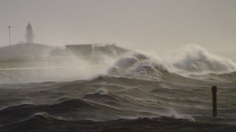 Large sea waves hitting a wall.