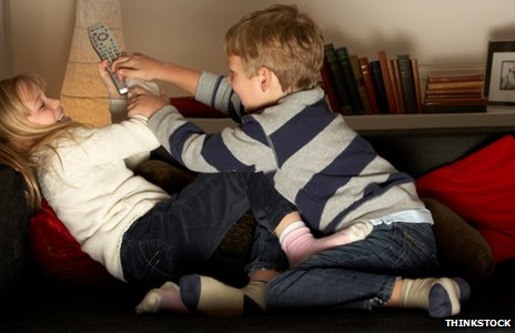Two children fighting over a remote