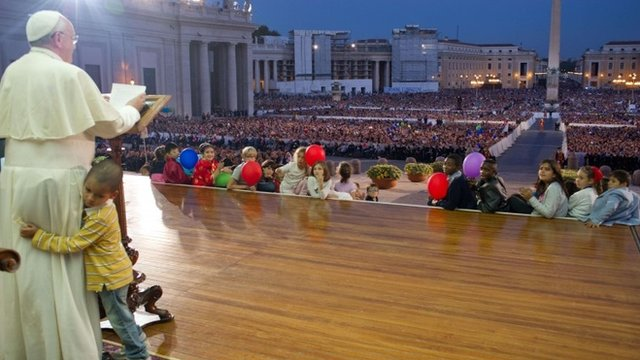 A handout picture taken on October 26, 2013 and released by Osservatore Romano on October 29, 2013 shows Pope Francis addressing the crowd at St Peter's square in the Vatican as a boy hugs him.