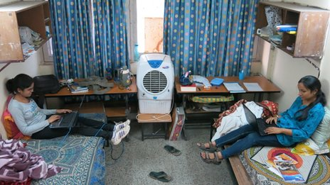 Two students sit on their beds with laptops