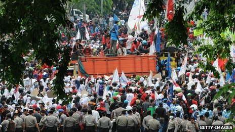 Protesters block the road while demonstrating to demand higher wages on 31 October 2013 in Surabaya