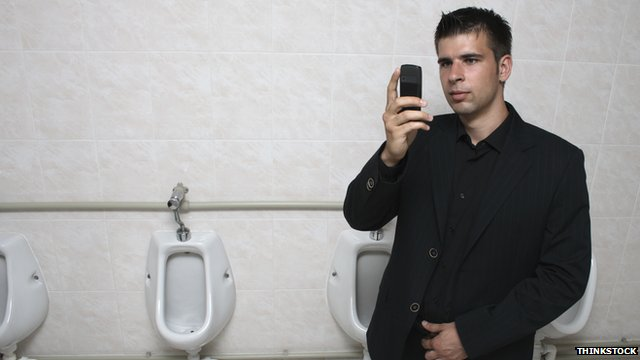 A man standing in a urinal taking a selfie