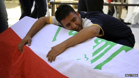 A man reacts on a coffin draped with an Iraqi flag during a funeral for victims of a bomb attack outside a cafe, in Najaf, on 21 October 2013