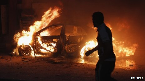 A man looks at a car on fire at the site of a bomb attack in Baghdad on 7 October 2013