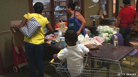 Jaden Painegua (2) watches as his mother at the West Side Campaign Against Hunger food pantry as his mother shops for food 24 July 2013