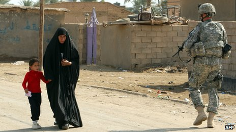 An Iraqi woman walks past a US soldier near a school in the town of Iskandiriyah, Iraq on 27 October 2011