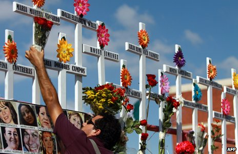 A relative of victims of the Casino Royale puts flowers on a cross during the commemoration of the first anniversary of the crime in Monterrey, Mexico, on August 25, 2012