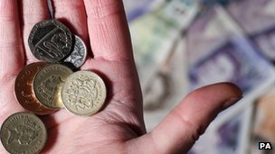 Hand holding pound coins