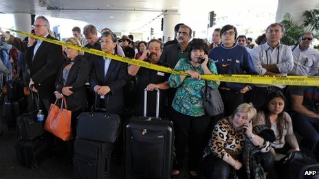 Departing passengers wait to enter the airport following a shooting incident earlier in the day which left one dead and others wounded, at Los Angeles International Airport, 1 November 2013 in Los Angeles, California