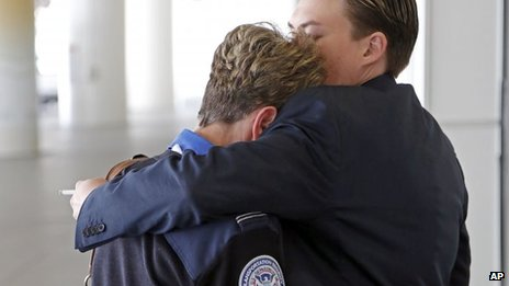 Transportation Security Administration employees hug outside Terminal 1 at Los Angeles International Airport on 1 November 2013