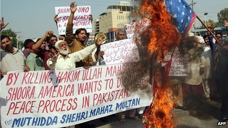 A Pakistani protester from United Citizen Action (UCA) holds a burning US flag as others shout anti-US slogans during a protest against the killing of Taliban leader Hakimullah Mehsud in a US drone attack